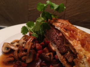 Venison Wellington with Caramelised Red Onion Gravy, Roasted Seasonal Mushrooms & Pancetta.
